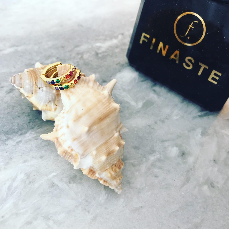 Gouden oorringetjes met gekleurde steentjes op schelp
