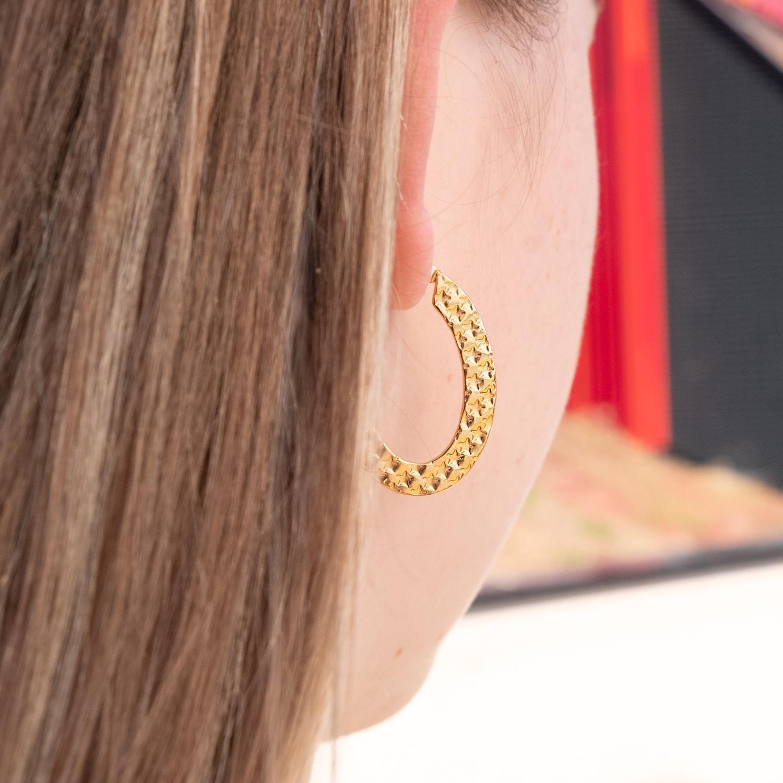 gouden oorringen met print bij vrouw met blonde haren