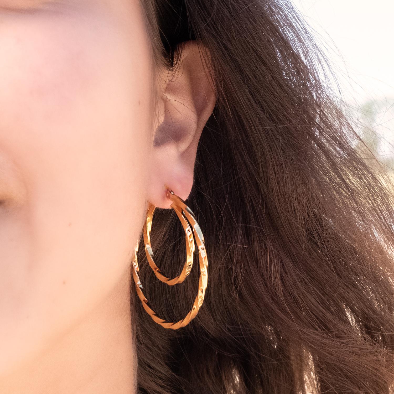 Vrouw draagt gouden dubbele oorringen bij donker haar