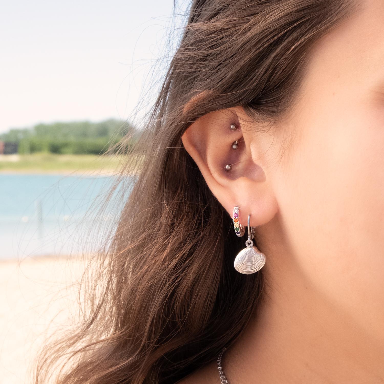 oorringetjes met gekleurde steentjes bij vrouw met oorringen