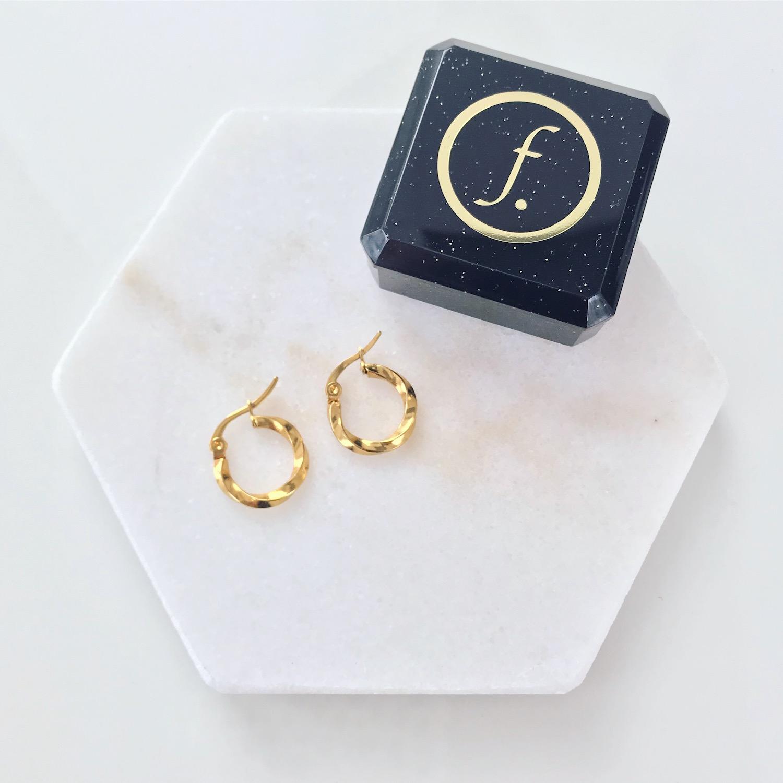 Gouden twist oorringetjes op marmeren ondergrond met sieradendoosje