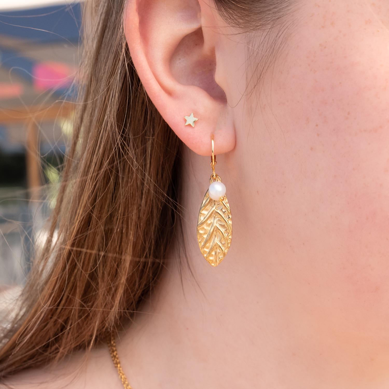 Vrouw draagt gouden oorringetjes met hanger