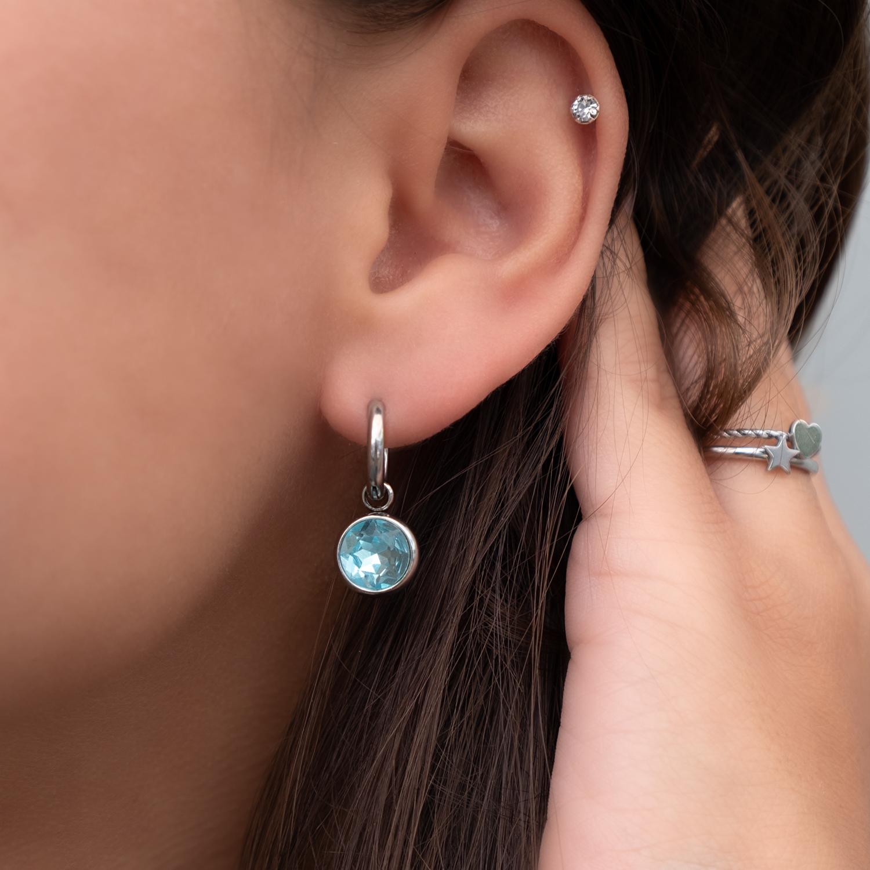 Vrouw met donker haar draagt oorringetjes met blauwe steen in het oor