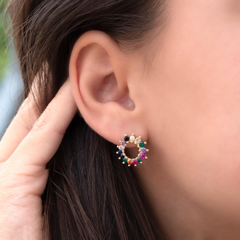 Vrouw draagt ronde regenboog stud oorbellen in het oor