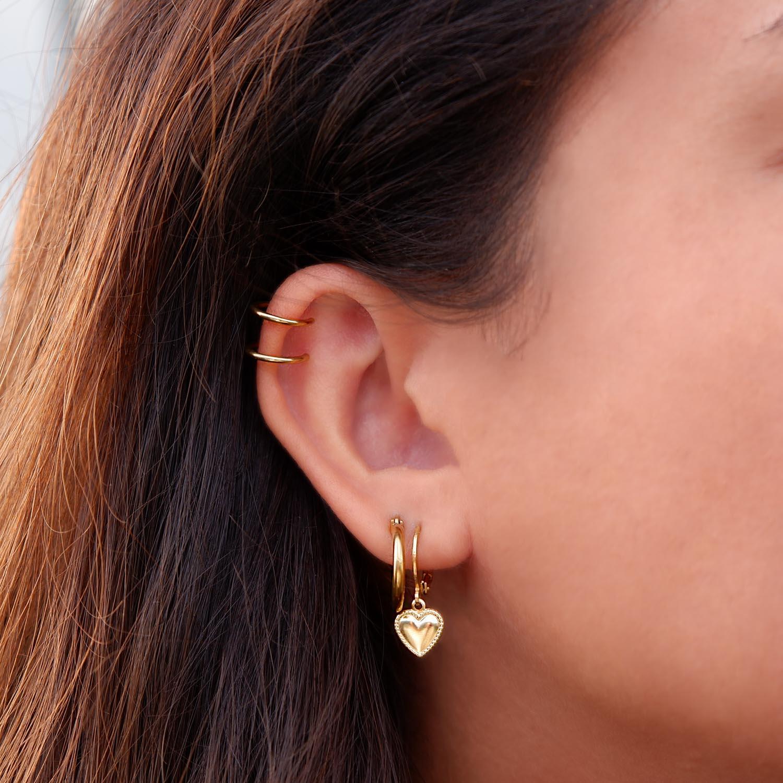 Leuke gouden oorringetjes in het oor met een ear cuff