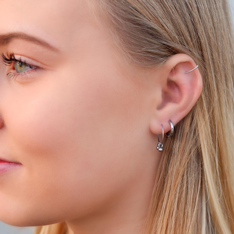 zilveren oorbellen in het oor met bolletjes