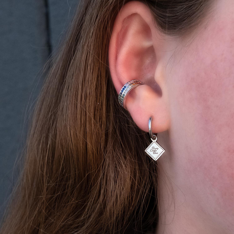vrouw draagt regenboog ear cuff in het oor