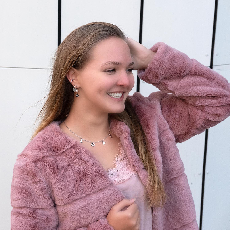 Vrouw draagt een zilveren love ketting om haar hals