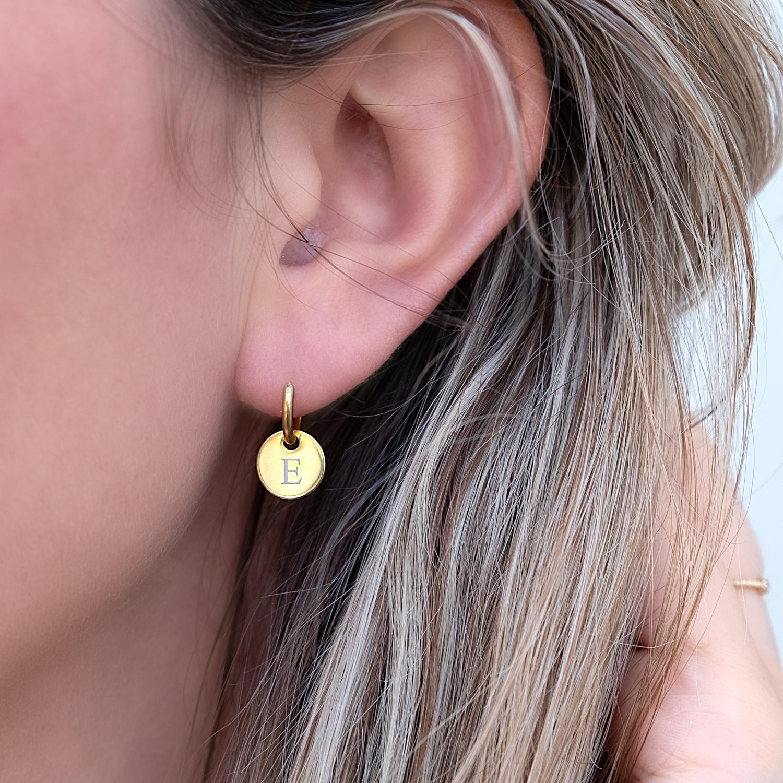 Gouden graveerbare initial oorringetjes in het oor met letter