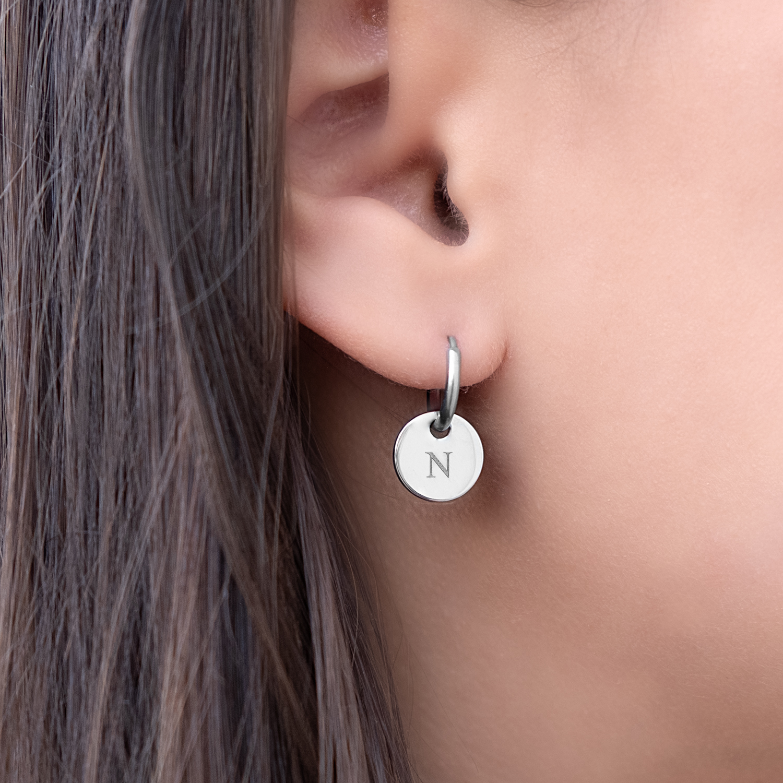 Graveerbare zilveren oorbellen in het oor bij vrouw met donker haar