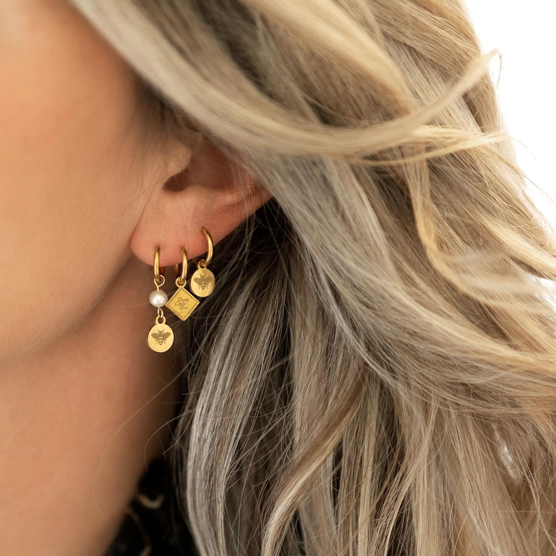 Leuke serie met gouden oorbellen in het oor met een mooie look