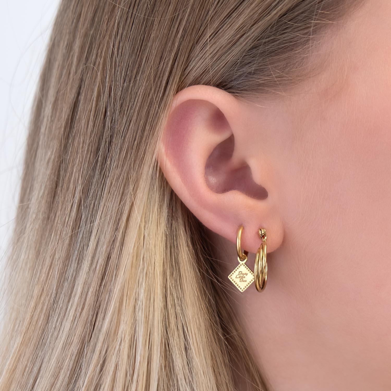 Vrouw draagt gouden oorbellen in het oor voor een complete look