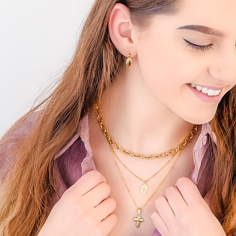 Vrouw draagt gouden oorbellen voor een complete look