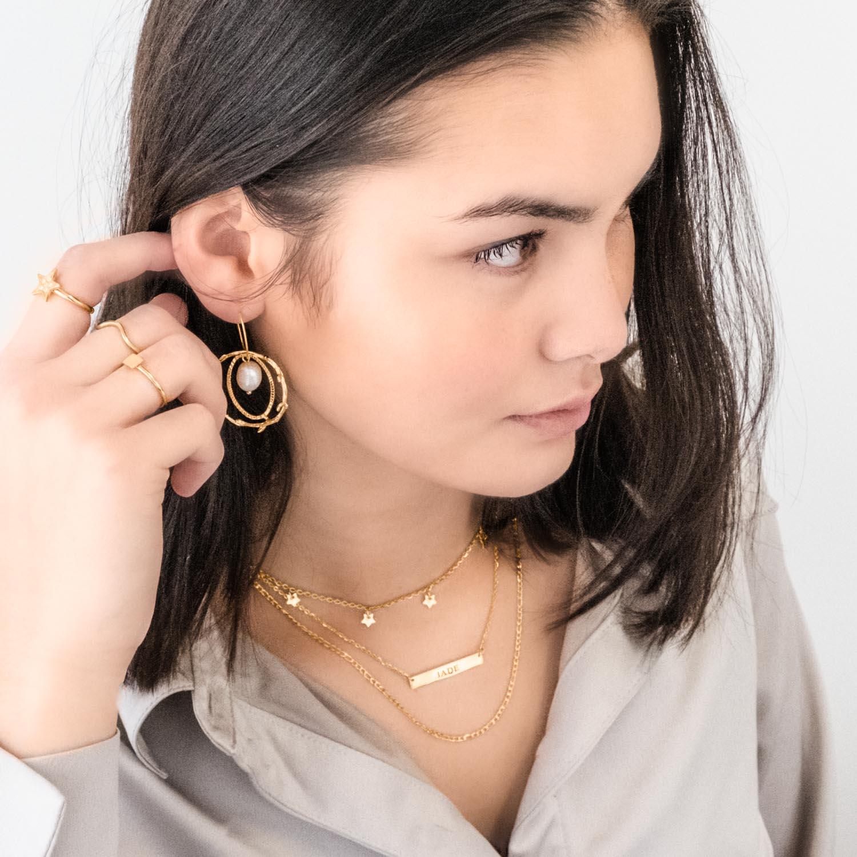 Leuke mix van gouden sieraden om de hals van jonge vrouw