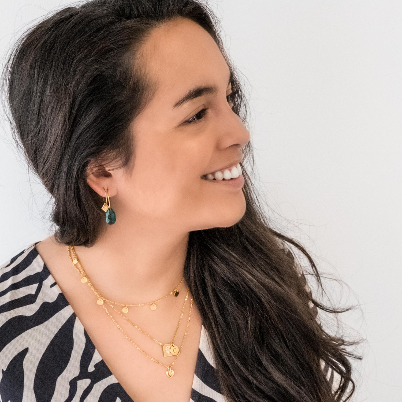 Vrouw draagt een leuke mix van gouden sieraden om
