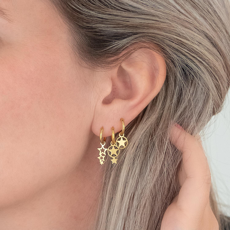 Gouden earparty in het oor met sterren voor een trendy look