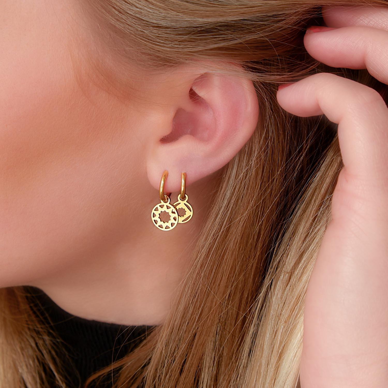 Gouden oorbellen in het oor voor een complete set