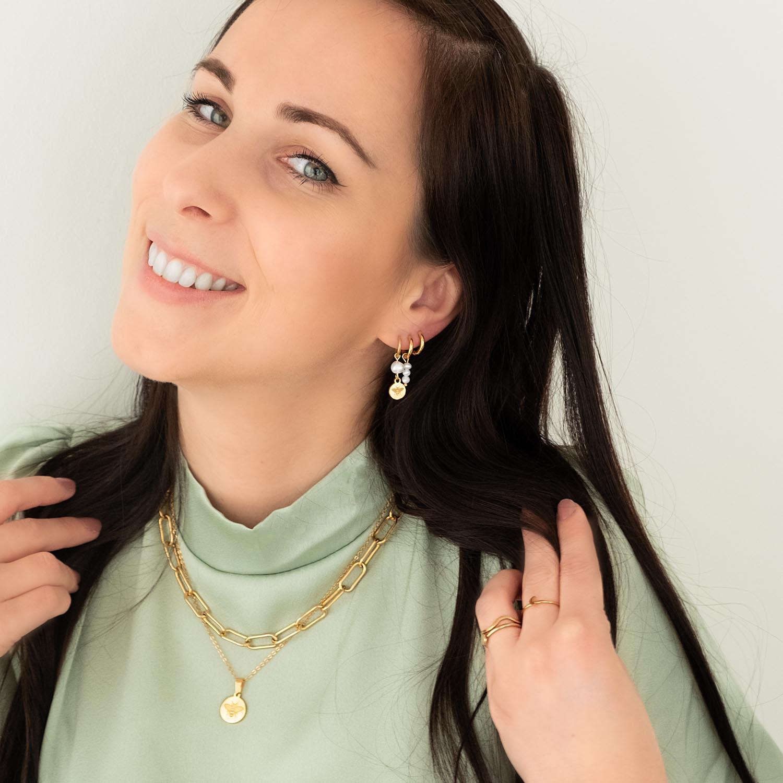 vrouw met donker haar draagt oorringetjes met parels in het oor