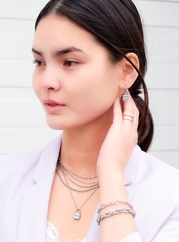 zilveren kettingen in een trendy look om de hals bij een paarse blazer