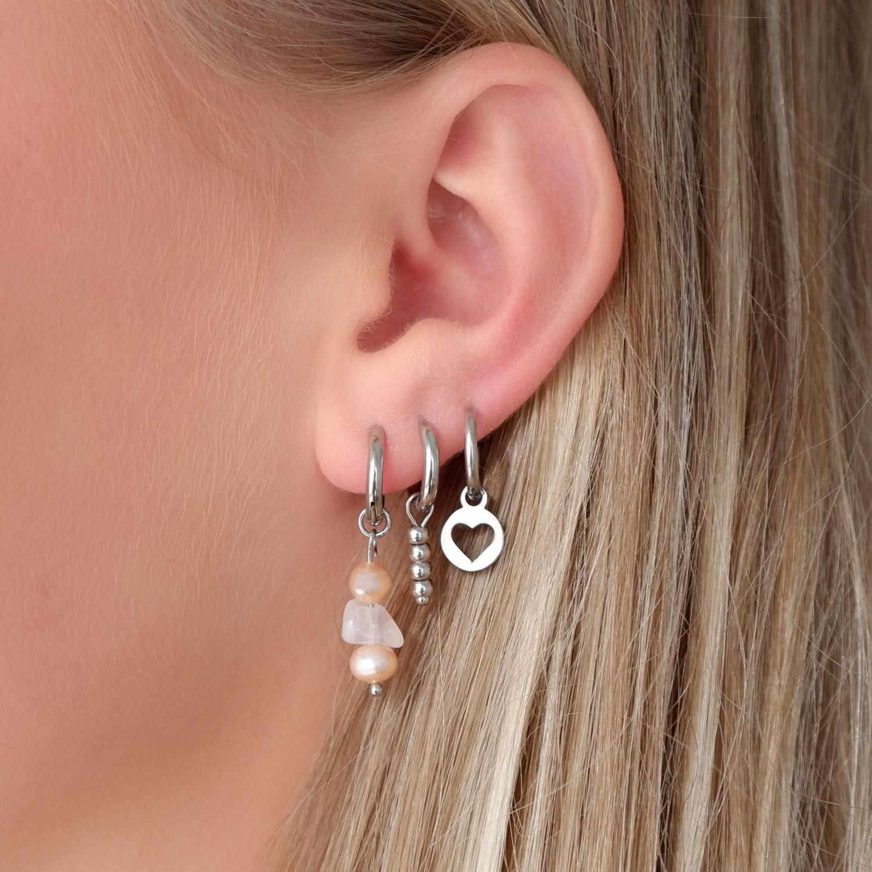 Trendy oorbellen met parel in het oor voor een complete earparty