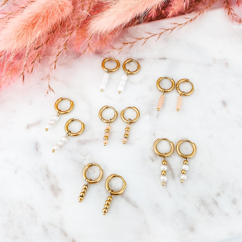 Trendy gouden oorbellen met ringetjes op marmer