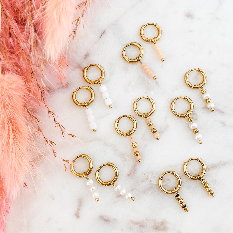 gouden oorringetjes met steentjes op een marmeren plaat
