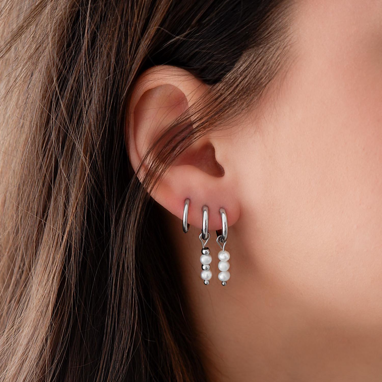 trendy oorbellen met parels in het oor voor een complete look
