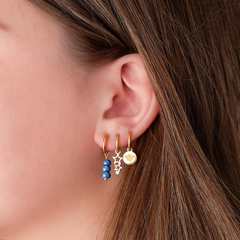 Trendy gouden oorbellen in het oor met drie gaatjes