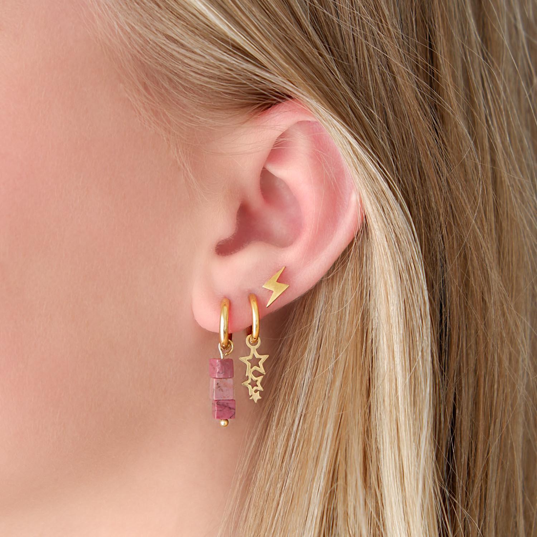 Trendy gouden oorringetjes in het oor voor een complete look