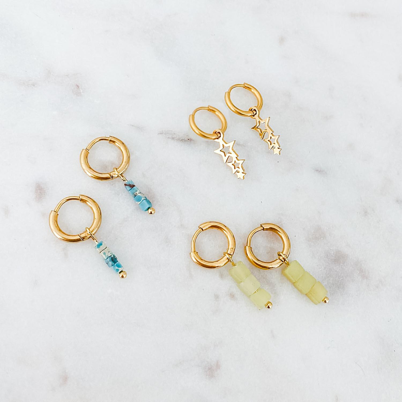 Gele oorbellen met steentjes in het oor voor een trendy look