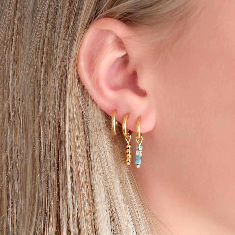 Gouden oorringetjes in het oor voor een trendy look