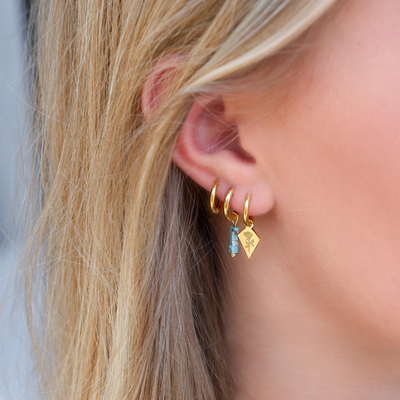 Goud kleurige hanger oorbellen met roosje en quote