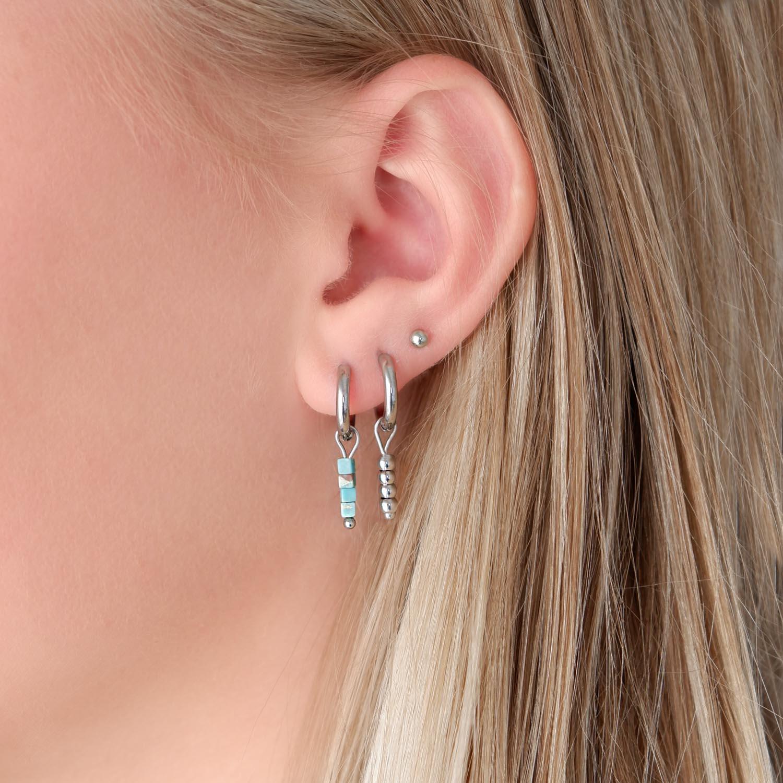 Trendy zilveren oorringetjes in het oor voor een complete look