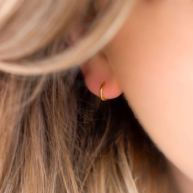 Trendy oorringetjes in het oor van een vrouw