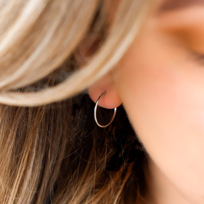 Trendy set met oorbellen in het oor bij een vrouw met blonde haren