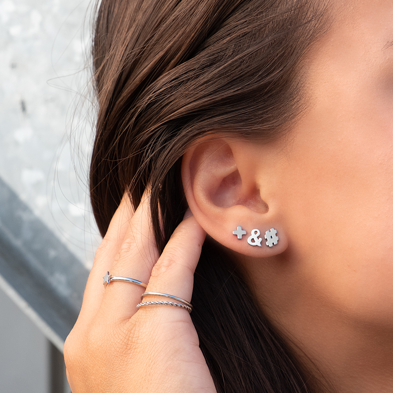 Zilveren oorbellen in het oor met studjes in een mix