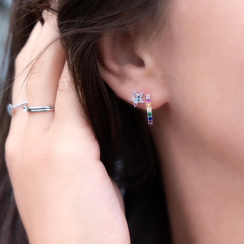 Vrouw draagt gekleurde oorringetjes samen met sterren