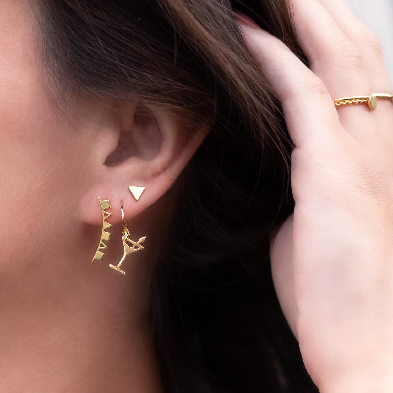 Vrouw draagt gouden stud oorbellen in het oor met cocktail glas