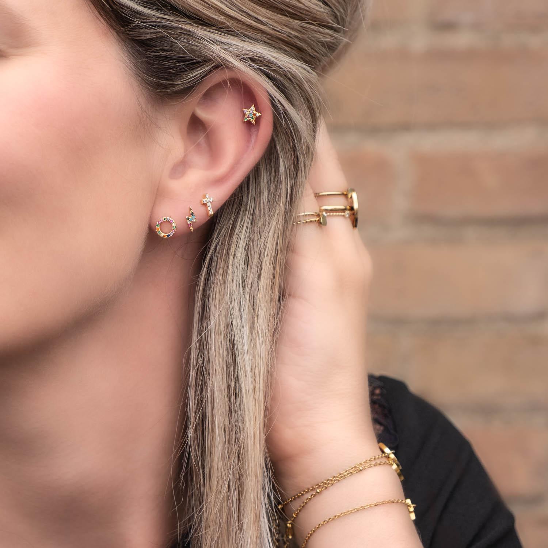 Vrouw met blond haar draagt regenboog stud oorbellen set