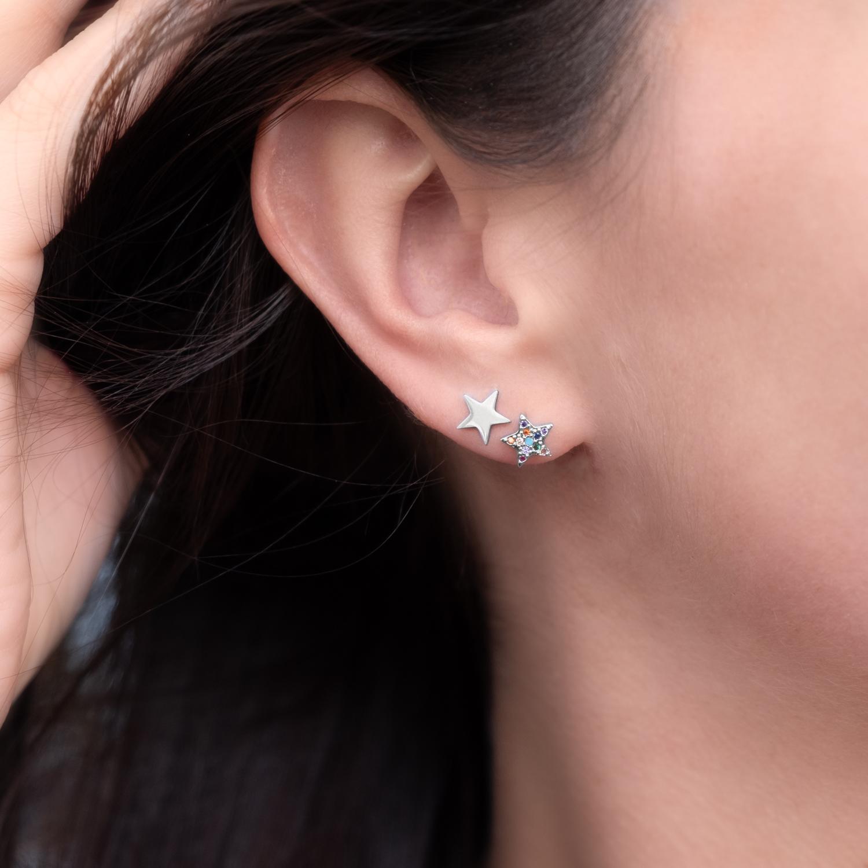 Vrouw draagt zilveren ster oorbellen in het oor met combinatie