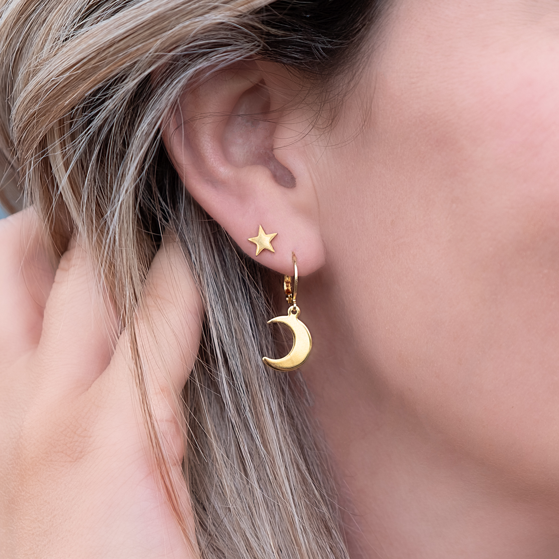 Vrouw draagt Maan en Ster oorbellen in het oor in het goud