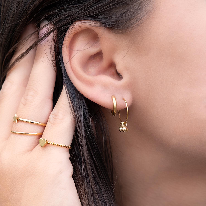 Vrouw draagt gouden oorringetjes voor de minimalistische trend