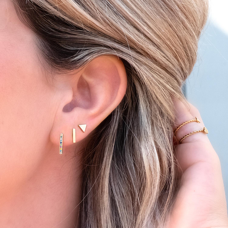 Mix van verschillende stud oorbellen in het oor in het goud